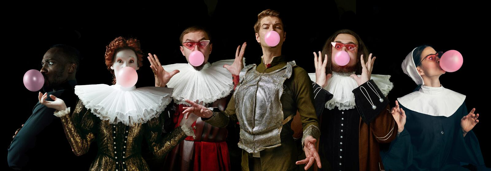 Young people as a medieval knights or grandees on dark background. Young people as a medieval grandee on dark studio background. Bubbling up of pink gum. Collage stock photo