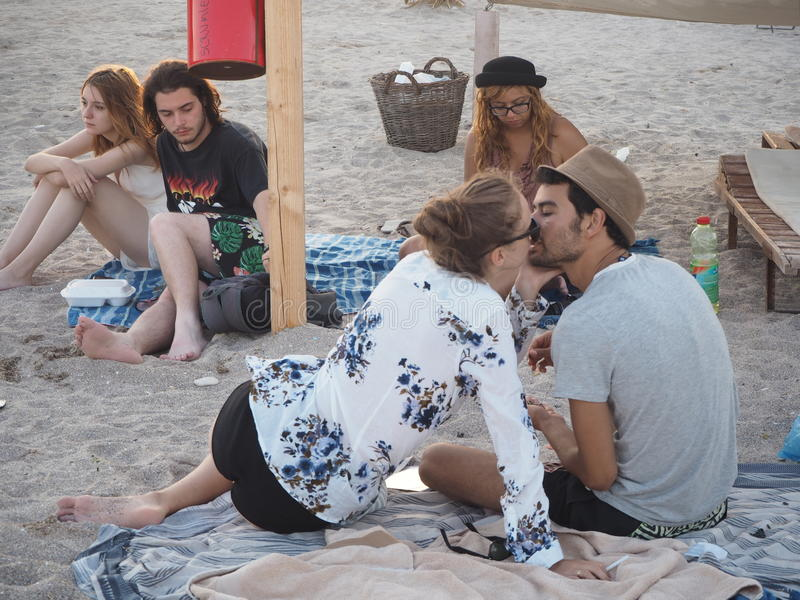 Young people on beach. Happy couple, upset couple and single girl sitting on sand in the evening on Vama Veche beach at the Black Sea in Romania, on August 27