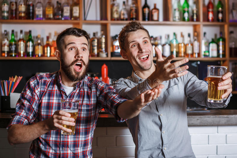 Young people with beer watching football in a bar stock images