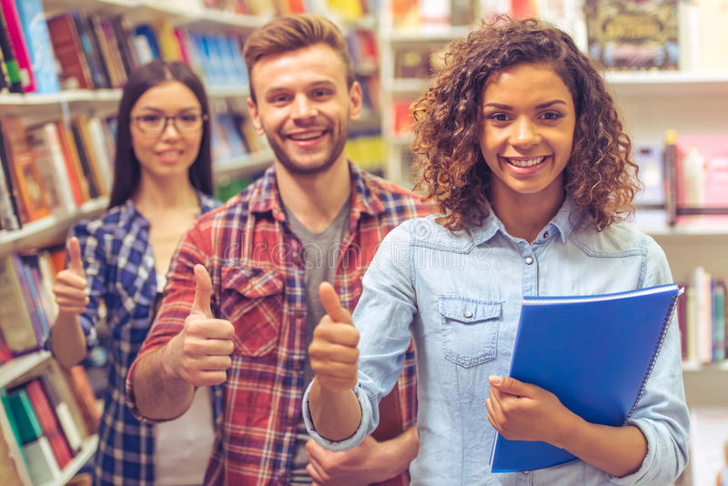 Young people at the book shop. Young people are holding books, showing Ok sign and smiling while standing at the bookshop one by one, Afro American girl in the royalty free stock image