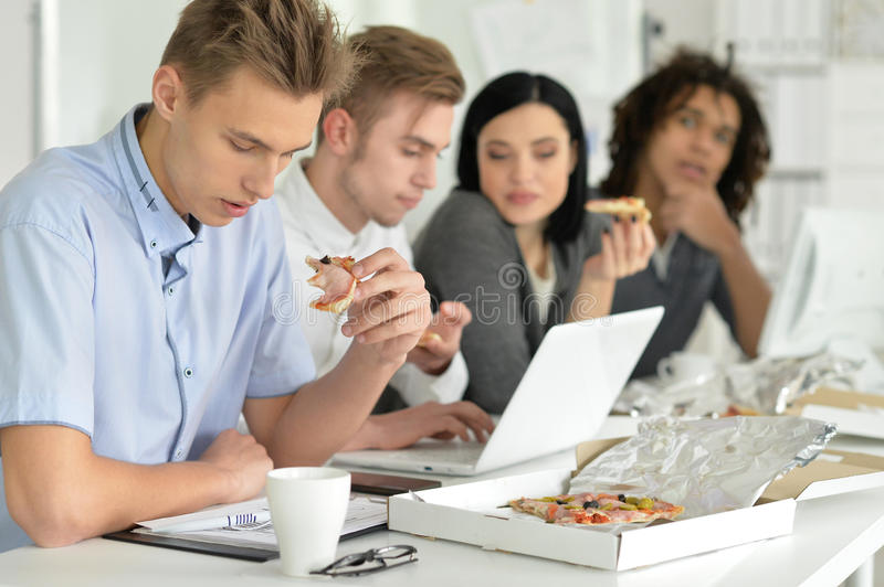 Young people on break. Portrait of a young people on break eating pizza royalty free stock images