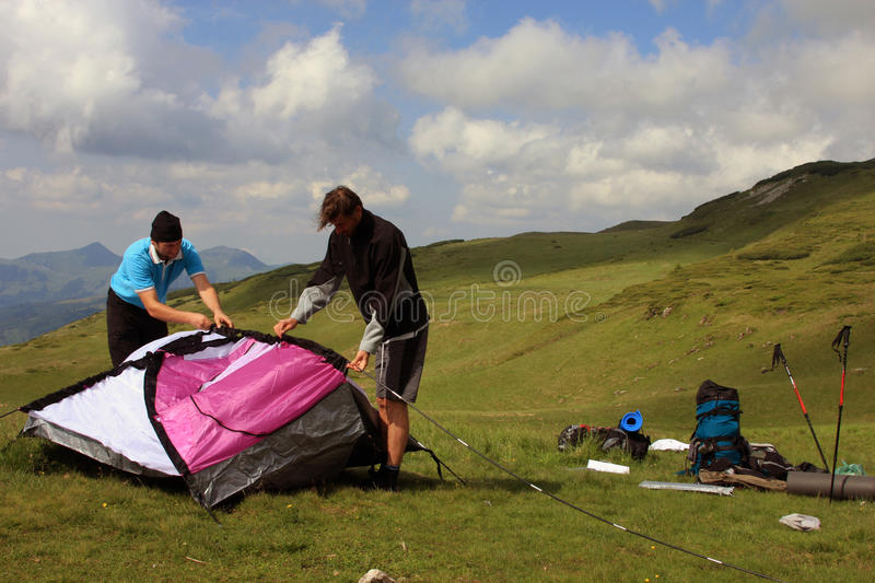 Young people building a tent on a mountain stock image