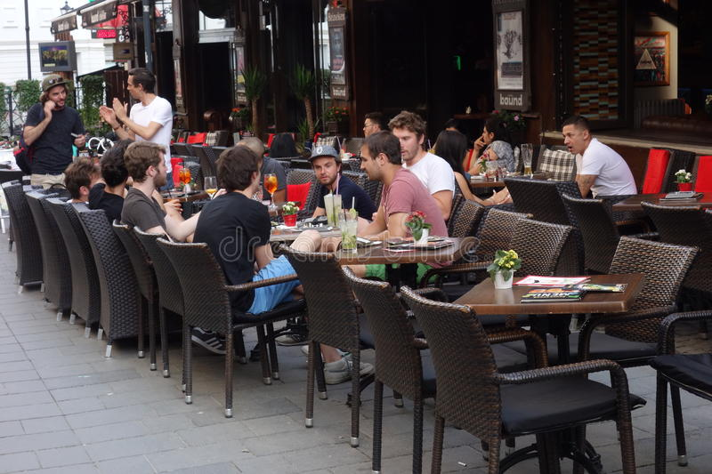 Young people at cafe's outdoor terrace in old center in Bucharest, Romania, on June 2, 2017 stock photo