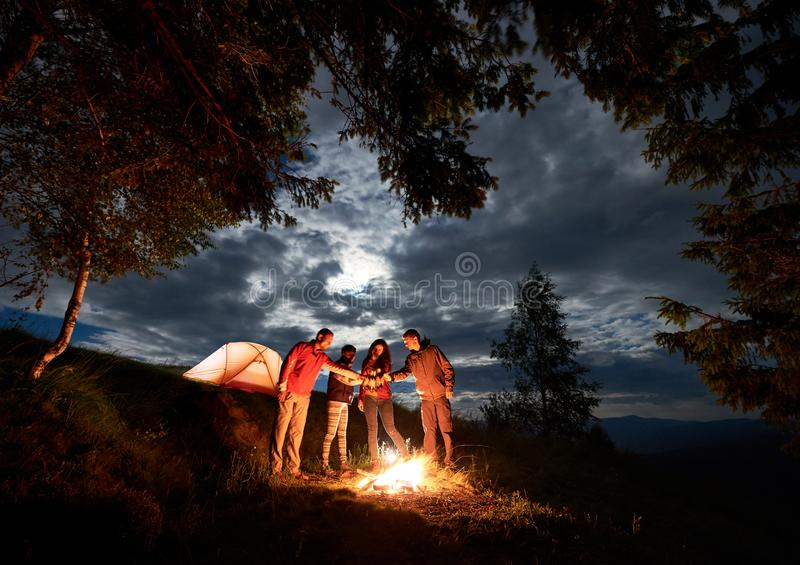 Young people celebrate holiday with beer by the fire near tent around the trees under cloudy sky. Young people backpackers celebrating holiday with beer by the royalty free stock images