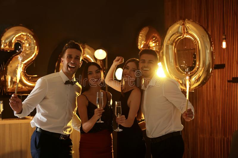 Young people celebrating New Year. Golden 2020 balloons on background royalty free stock photo