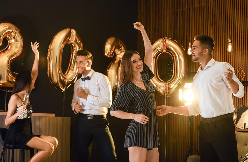 Young people celebrating New Year. Golden 2020 balloons on background royalty free stock photography