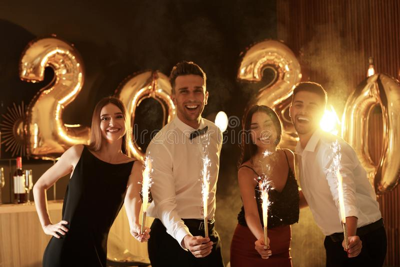 Young people celebrating New Year. Golden 2020 balloons on background stock photo