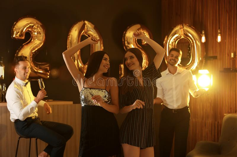 Young people celebrating New Year. Golden 2020 balloons on background stock photography