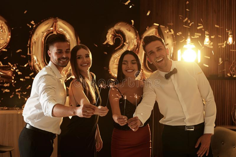 Young people celebrating New Year. Golden 2020 balloons on background stock images