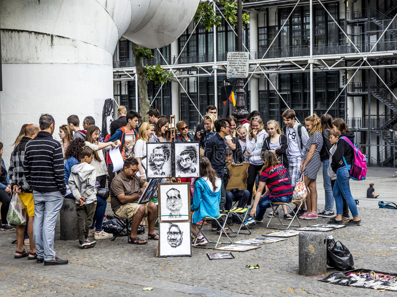 Young people at centre pompidou have fun being drawed by artists. PARIS, FRANCE - JUNE 9, 2015: young people at centre pompidou have fun being drawed by artists stock photography