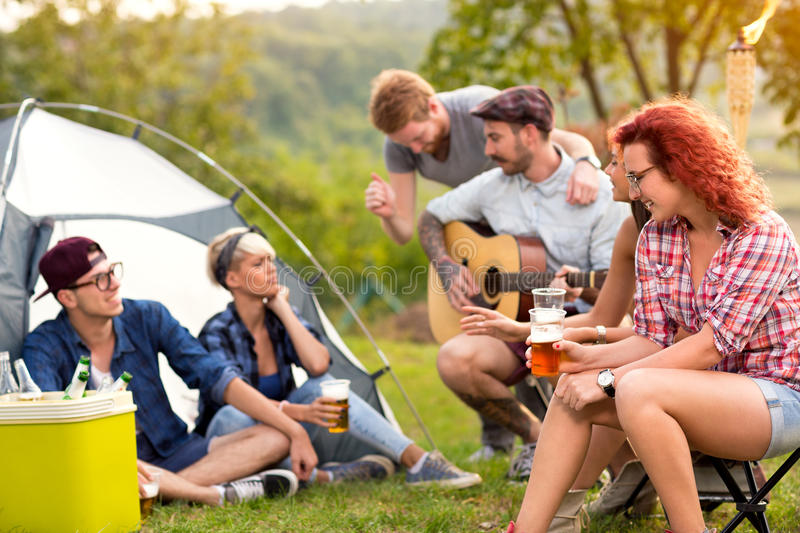 Young people chat, drink beer and play guitar. Young group of people chat, drink beer and play guitar in green nature royalty free stock photography