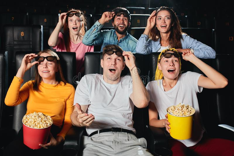Young people cheering up and laughing at funny comedy in cinema. royalty free stock image