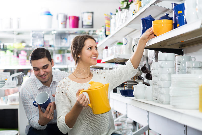 Young people chooses ceramic ware. In the cookware section at hypermarket stock photography