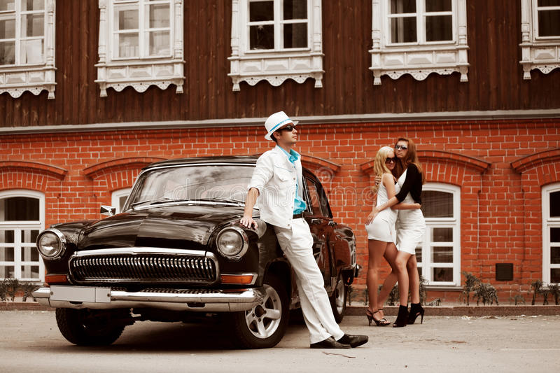 Young fashion people next to retro car stock photography