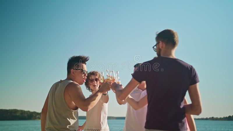 Young People Clinking Bottles on the Beach stock image