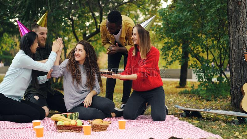 Young people are congratulating girl on birthday bringing cake laughing and rejoicing during outdoor party in park. royalty free stock images