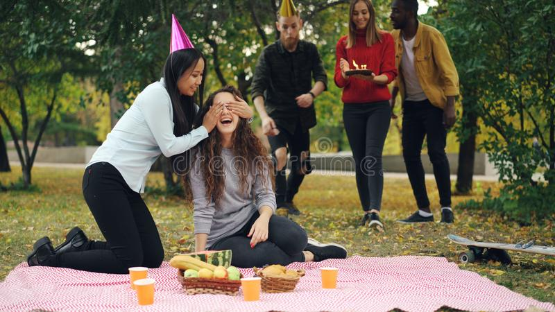 Young people are congratulating girl on birthday bringing cake laughing and rejoicing during outdoor party in park. Young people are congratulating happy girl stock image