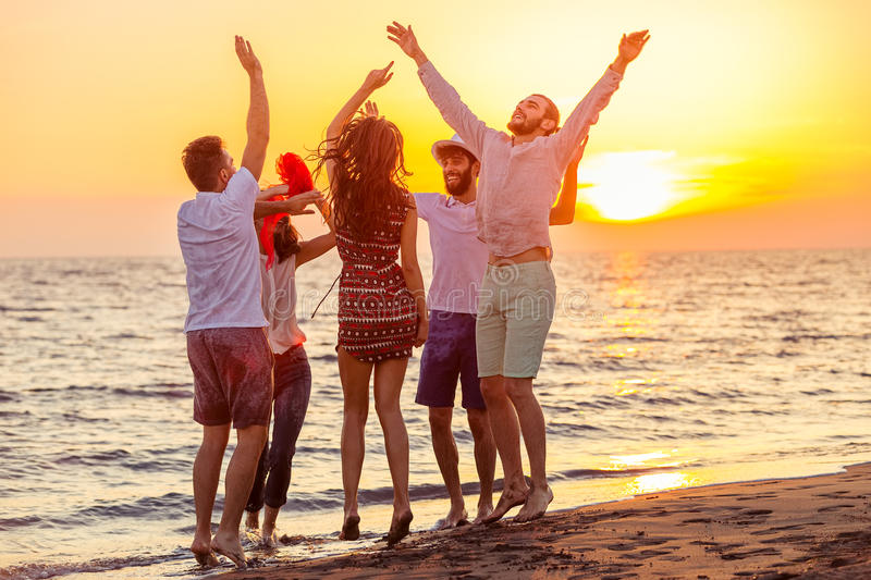 Young People Dancing On Beach at Sunset royalty free stock photos