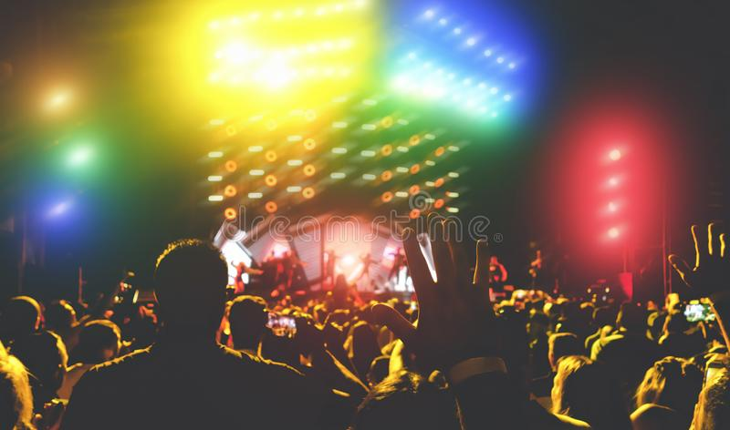 Young people dancing and having fun in music festival party outdoor - Crowd with hands up celebrating concert fest event stock photo