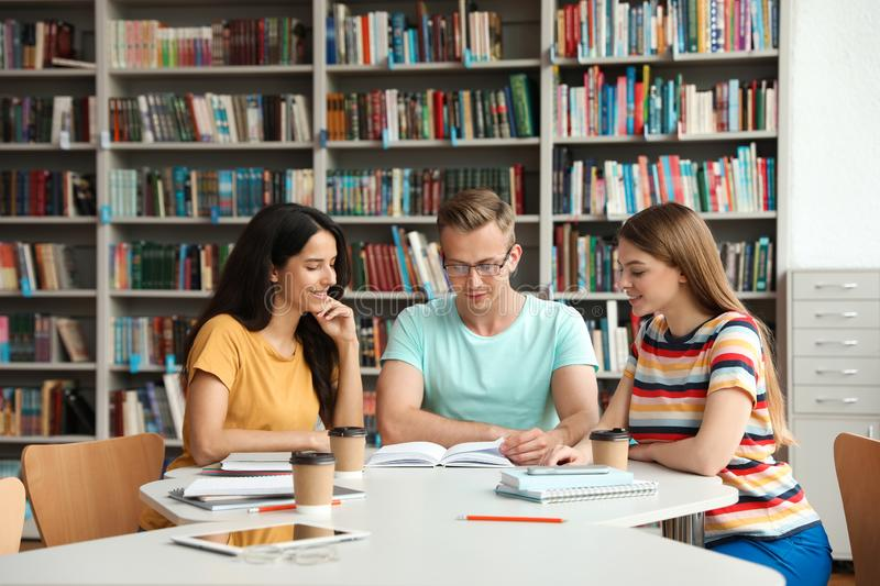 Young people discussing group project at table stock photos