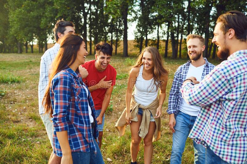 Young people drink and clink glasses at a picnic stock photography