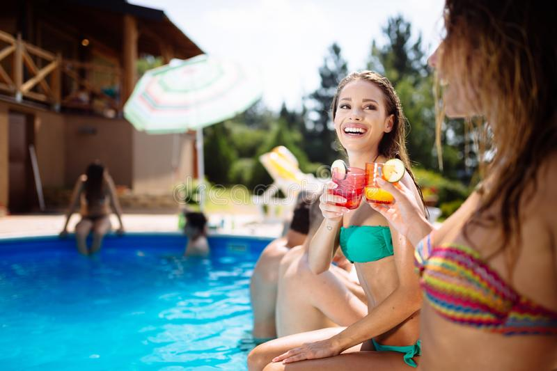 Young people drinking cocktails at swimming pool royalty free stock images