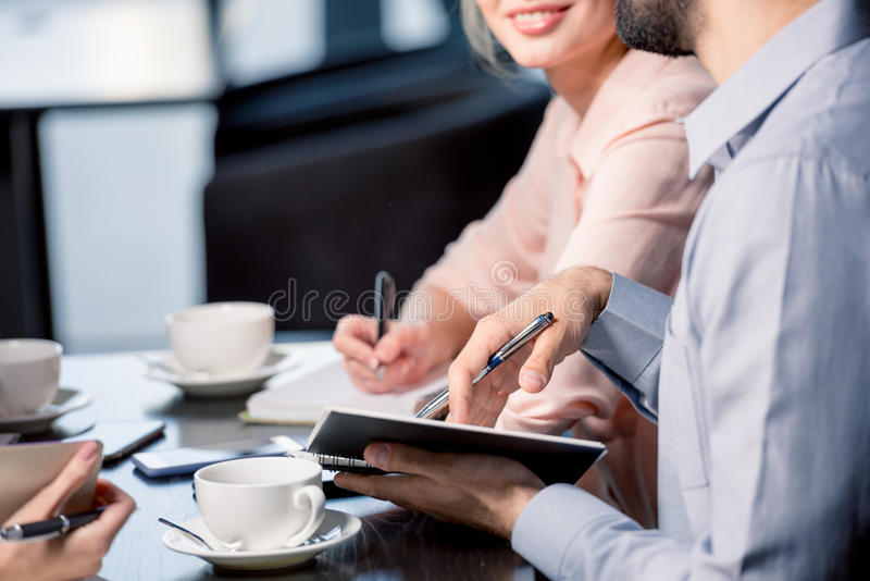 Young people drinking coffee and writing in notebooks at business meeting, business lunch concept royalty free stock image