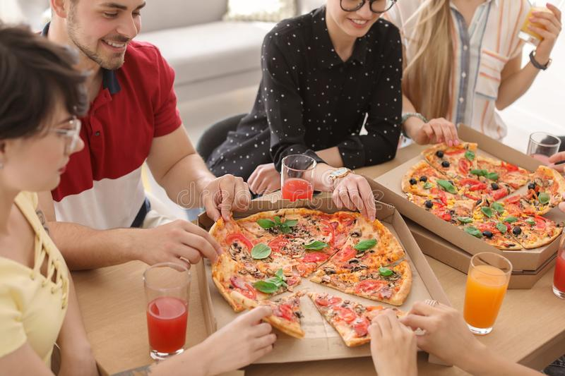 Young people eating delicious pizzas at table. Closeup royalty free stock photos