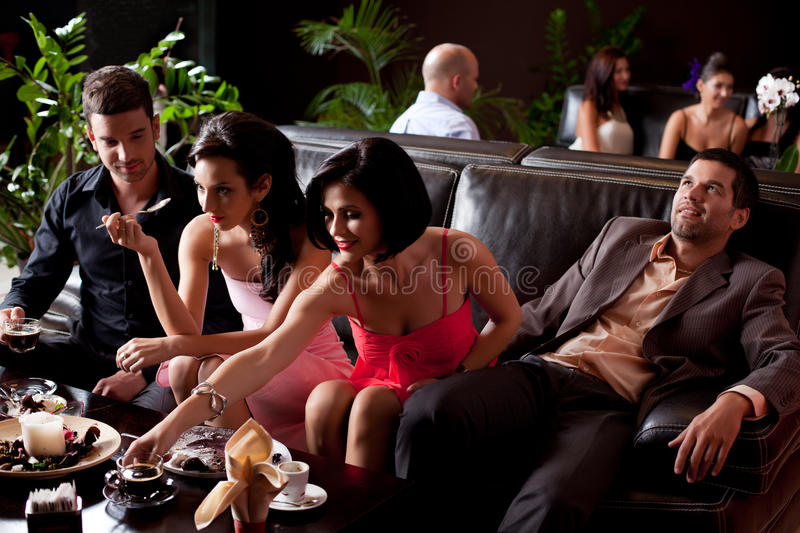 Young people eating deserts, man borred royalty free stock photo
