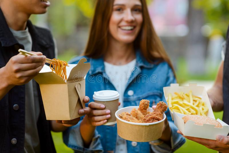 Young people eating fast food. Cropped photo of young people eating fast food, selective focus. Stir-fried noodles, fried chicken and French fries. Modern eating royalty free stock photos