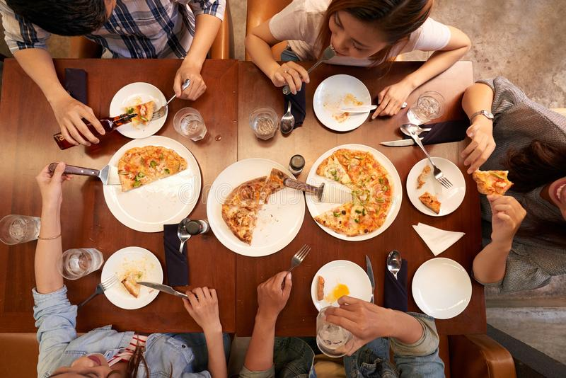 Young people eating pizzaa stock photography