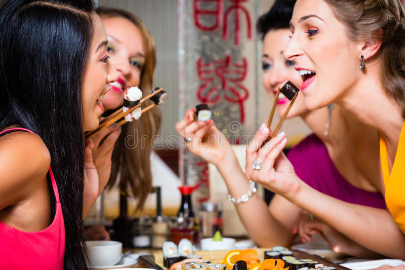 Young people eating sushi in restaurant royalty free stock photos