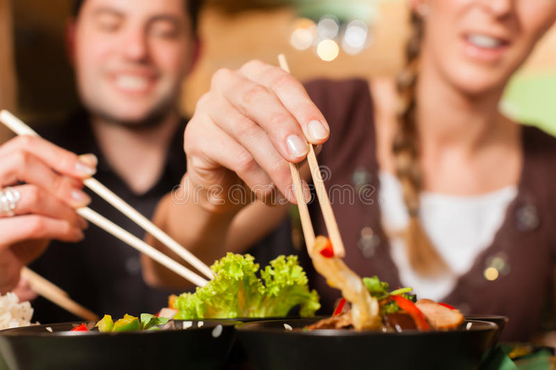 Young people eating in Thai restaurant. Young people eating in a Thai restaurant; they eating with chopsticks stock photo