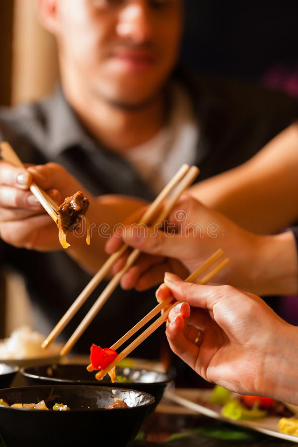 Young people eating in Thai restaurant. Young people eating in a Thai restaurant, they eating with chopsticks royalty free stock photography