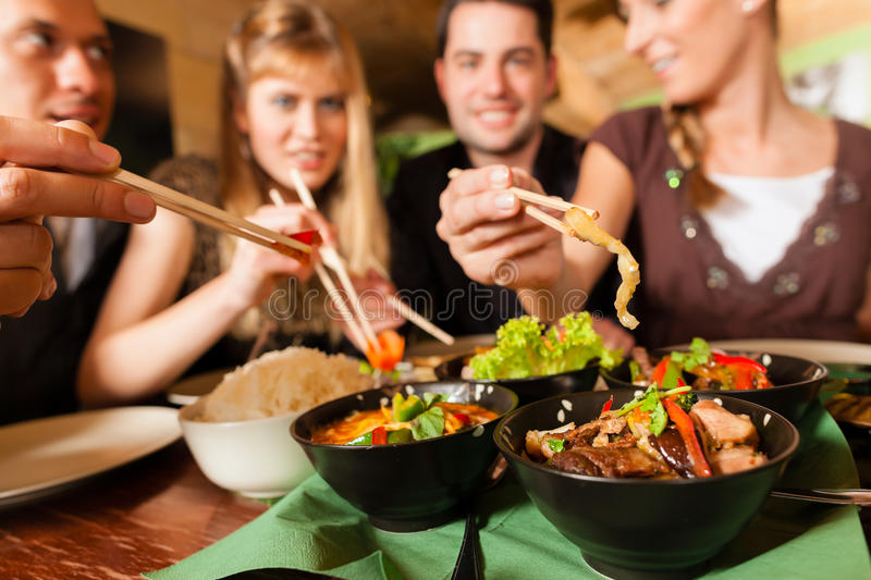 Young people eating in Thai restaurant. Young people eating in a Thai restaurant; they eating with chopsticks royalty free stock photo