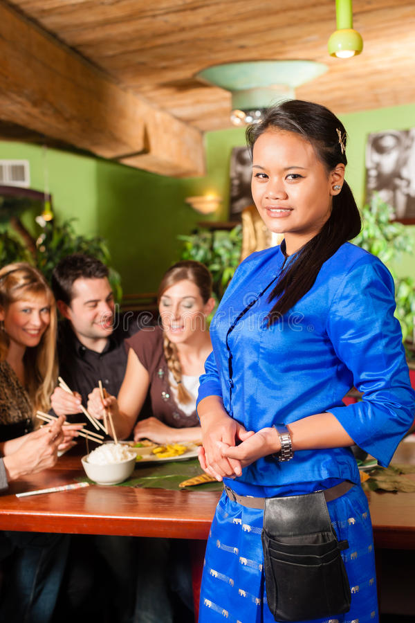 Young people eating in Thai restaurant. Young people eating in a Thai restaurant; the waitress brings the dishes, rice and others royalty free stock image