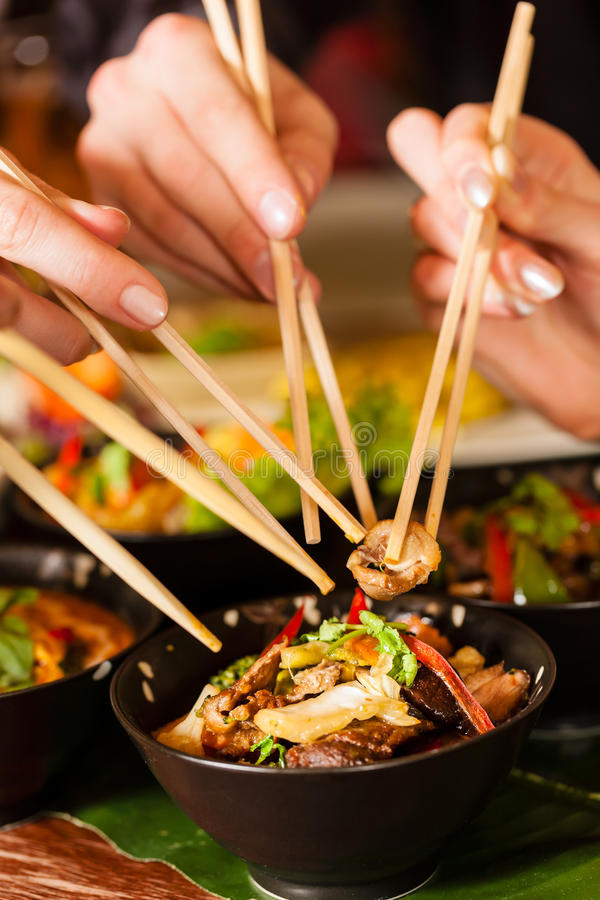 Young people eating in Thai restaurant. Young people eating in a Thai restaurant, they eating with chopsticks, close-up on hands and food stock images