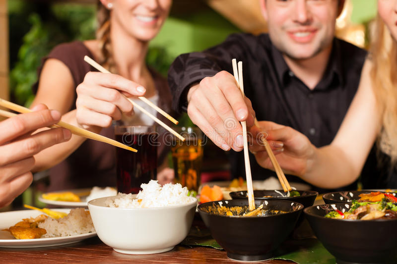 Young people eating in Thai restaurant. Young people eating in a Thai restaurant, they eating with chopsticks stock photography