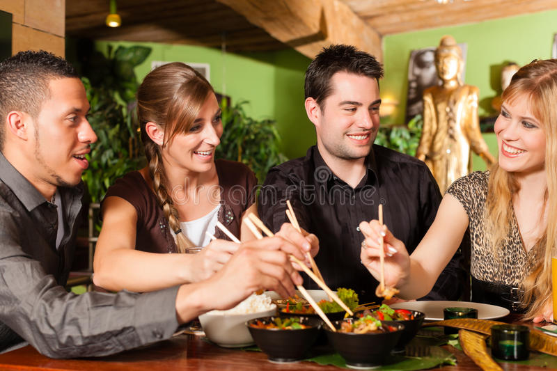 Young people eating in Thai restaurant. Young people eating in a Thai restaurant, they eating with chopsticks royalty free stock photos