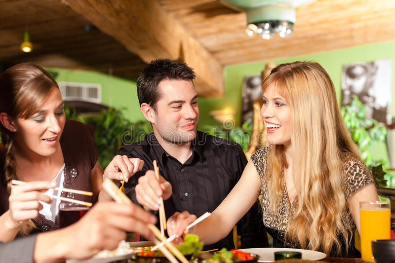 Young people eating in Thai restaurant. Young people eating in a Thai restaurant, they eating with chopsticks royalty free stock photo