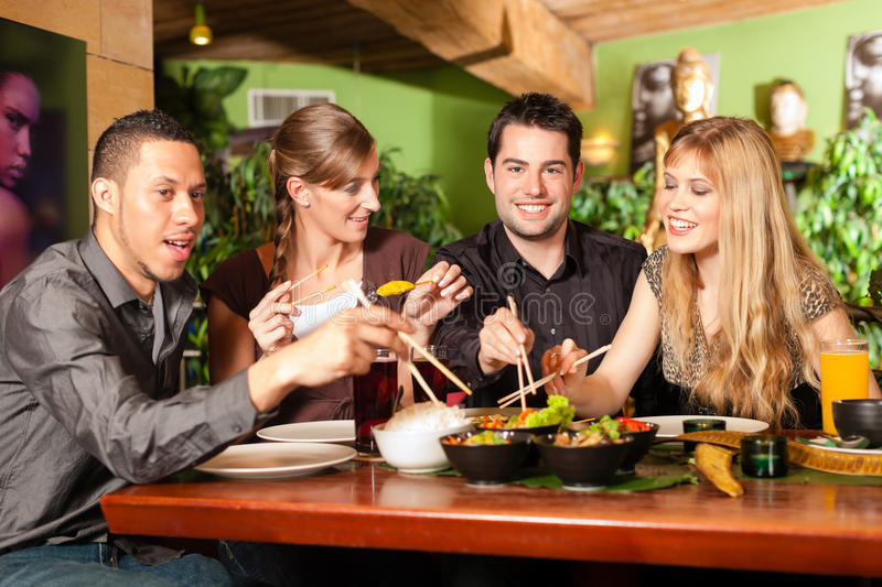 Young people eating in Thai restaurant. Young people eating in a Thai restaurant, they eating with chopsticks stock photo