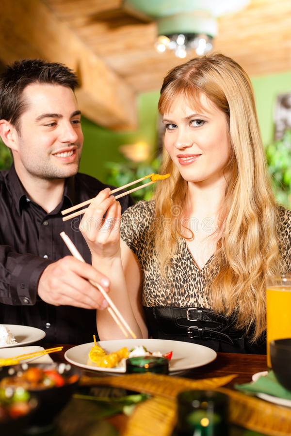 Young people eating in Thai restaurant. Young people eating in a Thai restaurant, they eating with chopsticks stock image