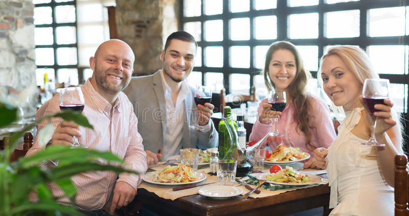 Young people enjoying food at tavern. Positive young people enjoying the food and smiling at the tavern stock photography