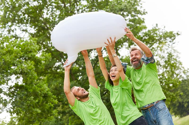 Young people in an environmental action. Three young people in an environmental action with a white balloon royalty free stock photography