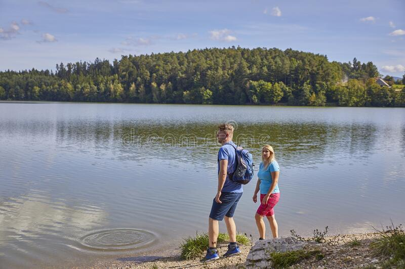 Young people get to the lake. CELJE, SLOVENIA - Sep 10, 2019: Two young people get to the lake on a nice sunny day and observe something in the distance royalty free stock photo