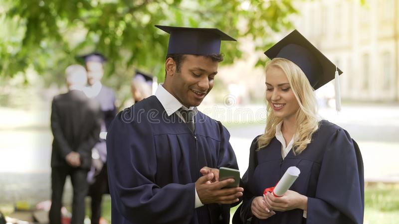 Young people in graduate uniform looking at phone screen, having discussion, job royalty free stock photos