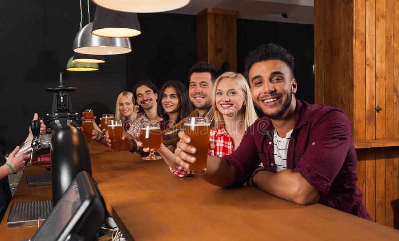 Young People Group In Bar, Hold Beer Glasses, Friends Sitting At Wooden Counter Pub, Toast royalty free stock photo