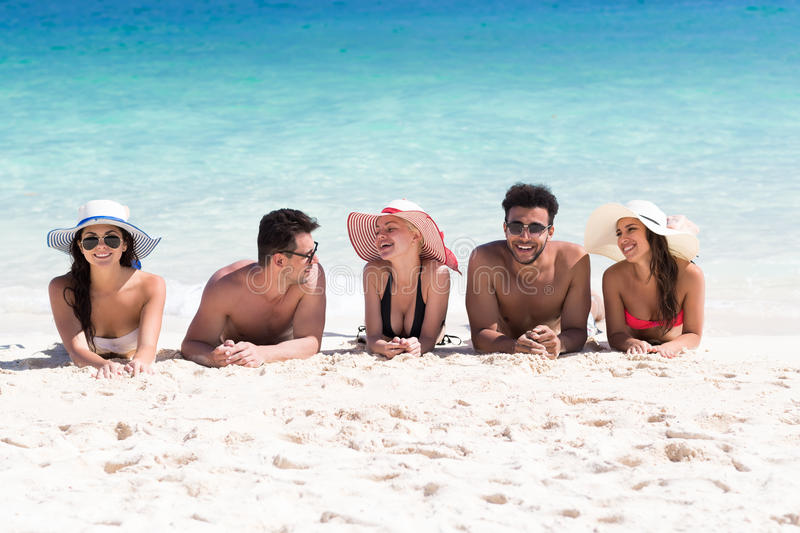 Young People Group On Beach Summer Vacation, Happy Smiling Friends Lying Sand Seaside royalty free stock photos