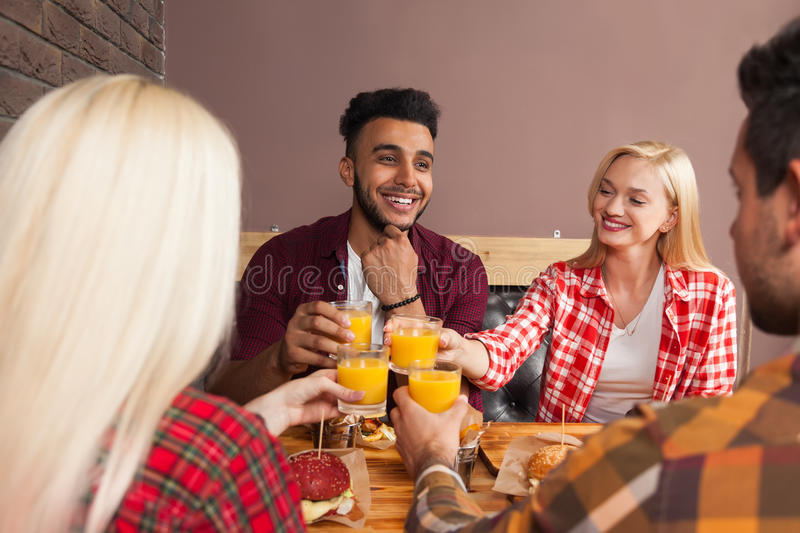 Young People Group Man And Woman Sitting In Burger Cafe, Toasting Orange Juice Order Fast Food On Wooden Table. Happy Smiling Fiends Meeting stock photography