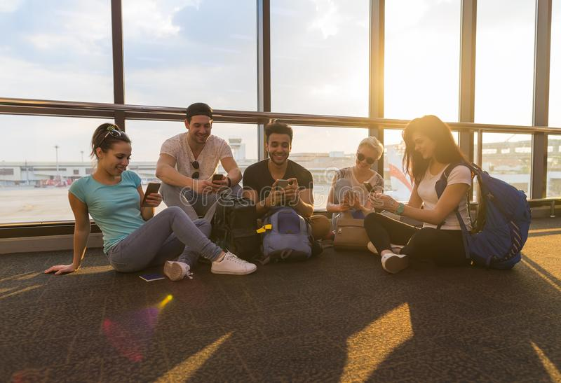 Young People Group Sitting On Floor Airport Lounge Waiting Departure Use Cell Smart Phone Chatting Mix Race Friends stock photo